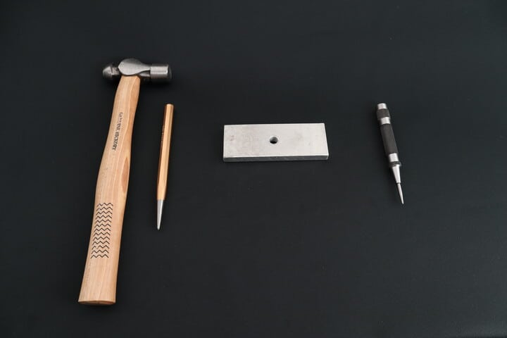 A manual center punch and a hammer compared to an automatic center punch